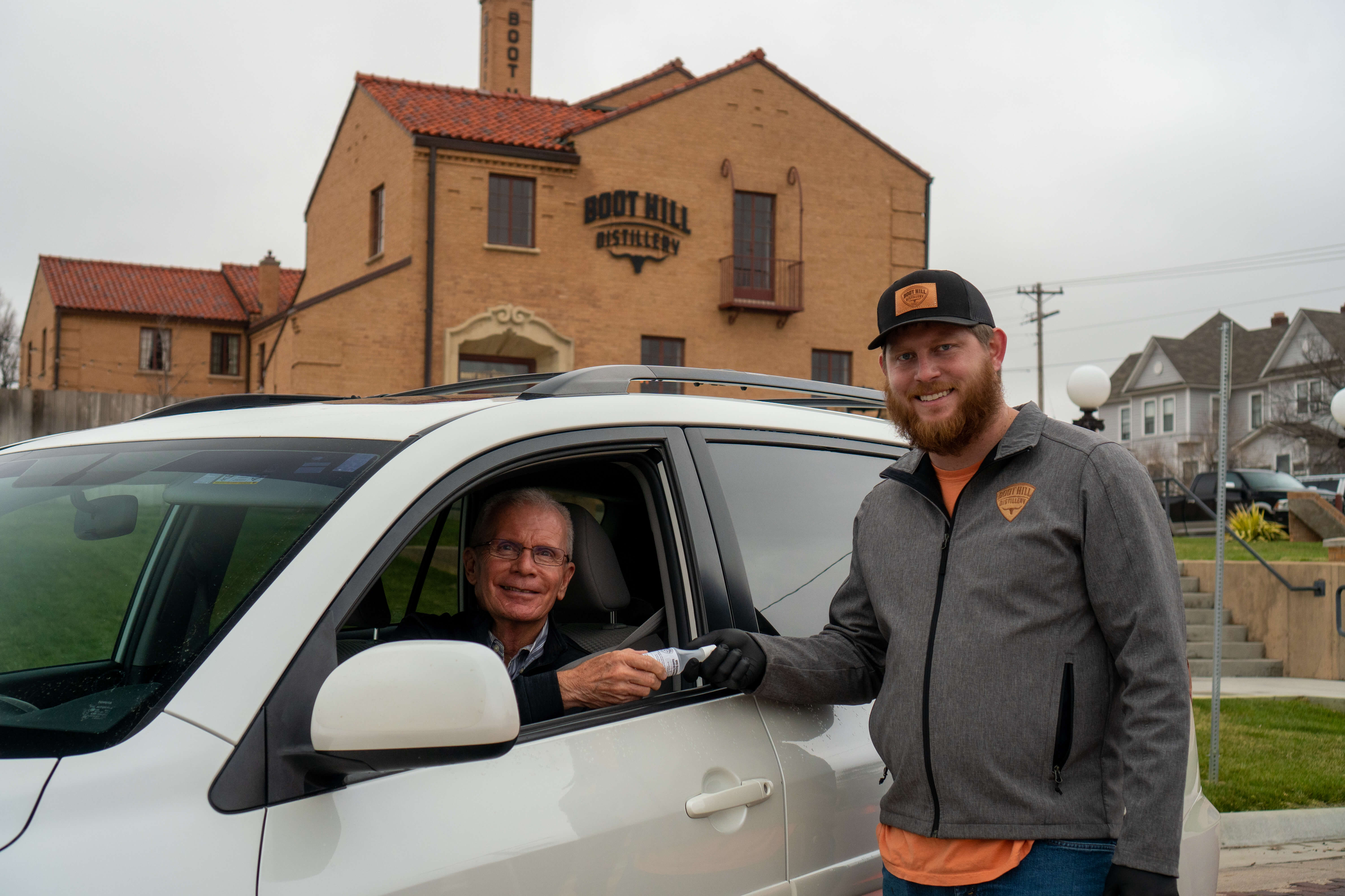 Hayes, Owner of Boot Hill Distillery, passes out hand cleanser in front of the distillery